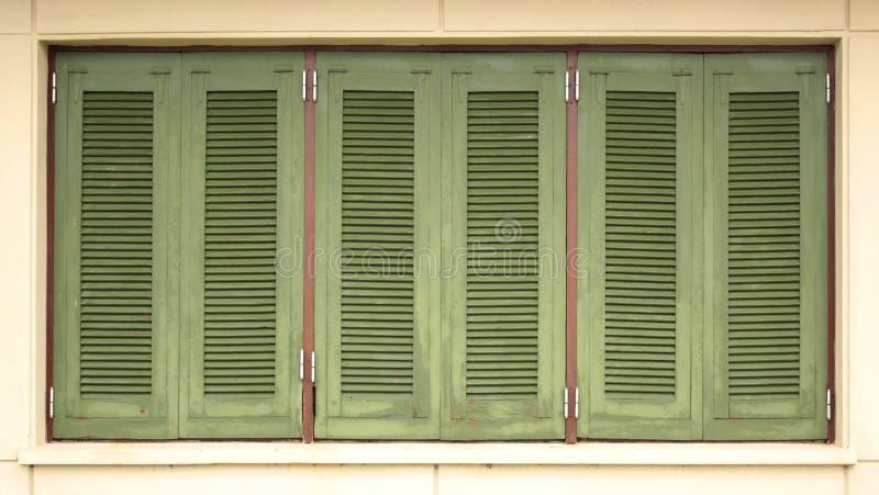 A casa verde shutters a vista tripla foto de stock royalty free