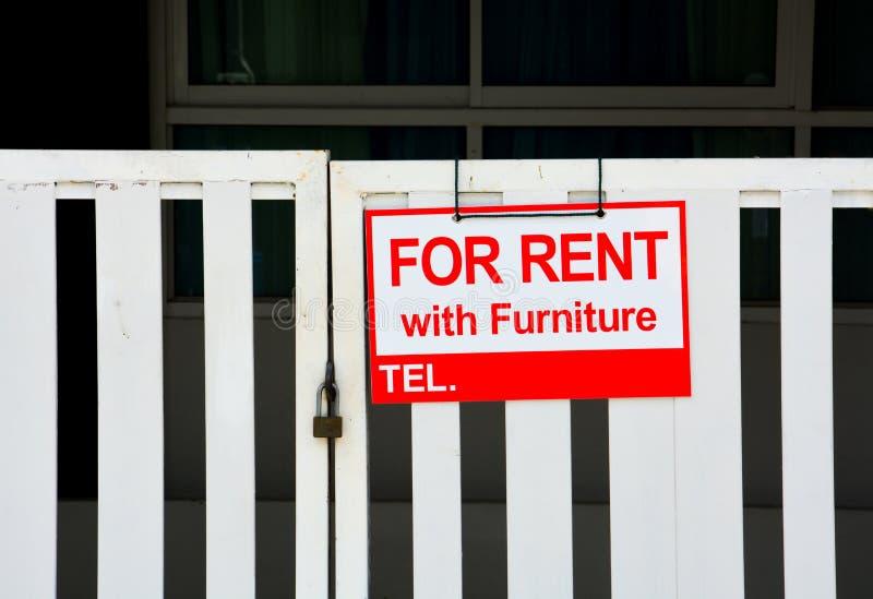 Casa vermelha para o aluguel com o sinal da mob?lia que pendura na cerca branca fechado, espa?o da c?pia fotos de stock royalty free