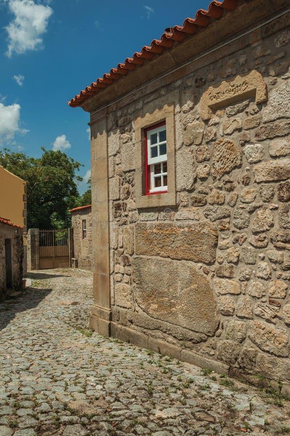 Casa vieja con la pared de piedra y la pequeña ventana en un callejón foto de archivo libre de regalías