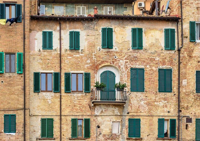 Casa vieja con las ventanas con los obturadores de madera en Siena Italia imagen de archivo libre de regalías