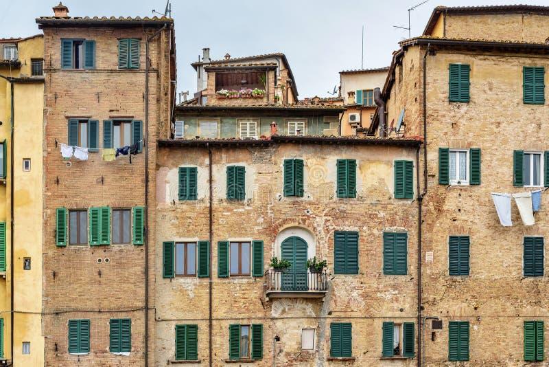 Casa vieja con las ventanas con los obturadores de madera en Siena Italia imagen de archivo