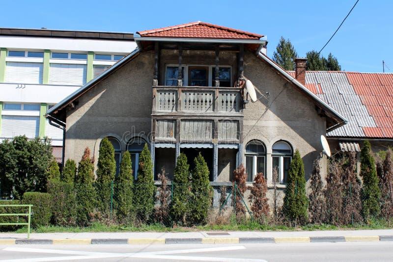 Casa vieja de la familia con la fachada dilapidada y el pórtico de madera rodeados con los árboles de ciprés en frente y los edif imagen de archivo