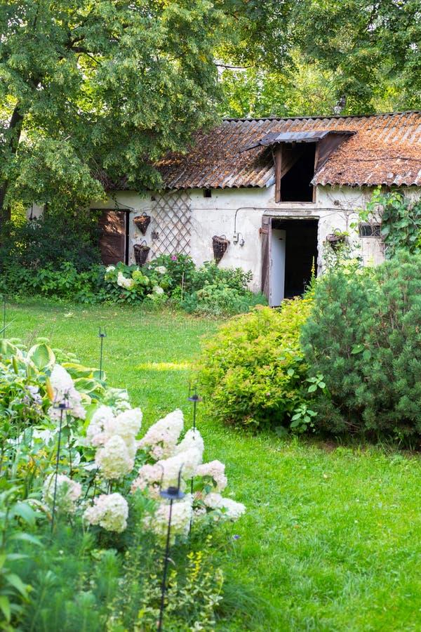 Casa vieja de la granja de la cabaña en jardín del verano foto de archivo