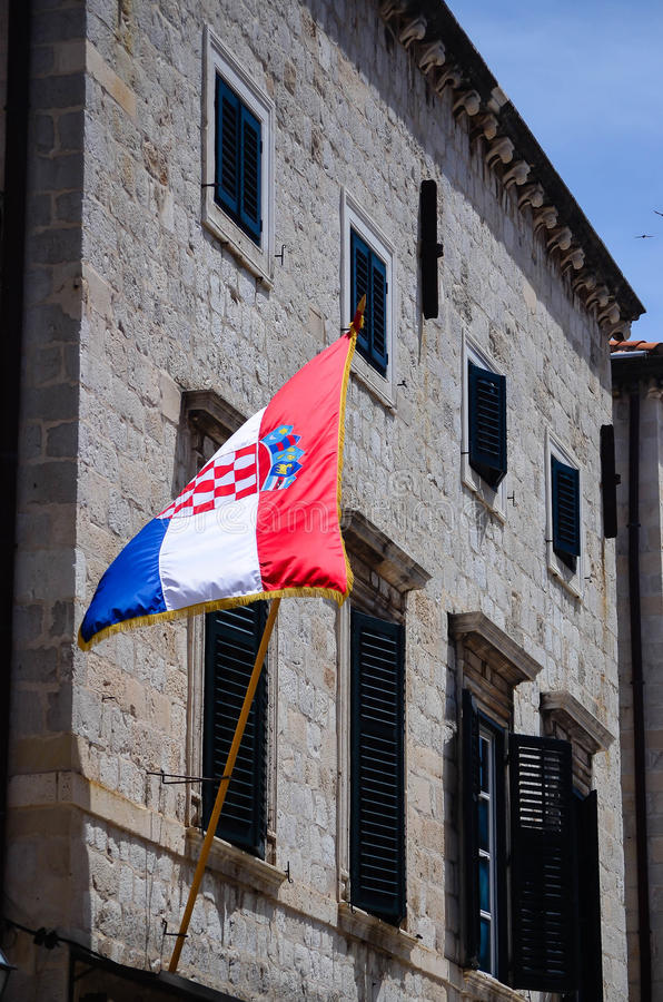 Casa vieja hermosa con la bandera croata en la calle que camina principal en la ciudad vieja de Dubrovnik imagenes de archivo
