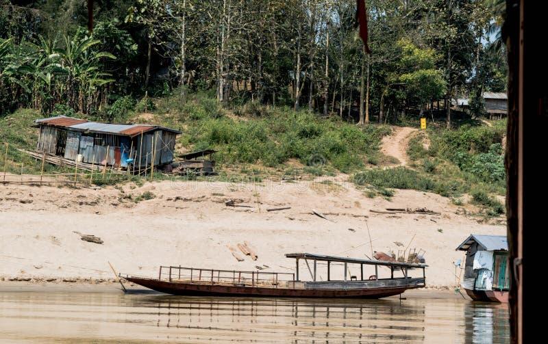 Casa y barco en la orilla del Mekong imagen de archivo