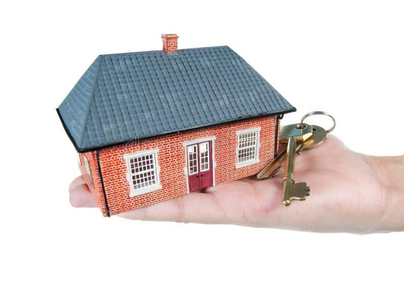 Casa y claves en una mano foto de archivo