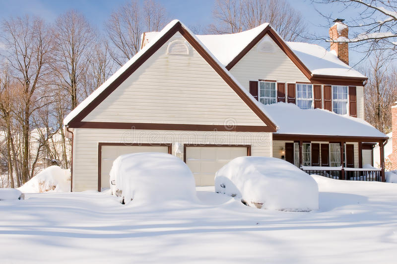 Casa y coches después de la tempestad de nieve imagen de archivo libre de regalías