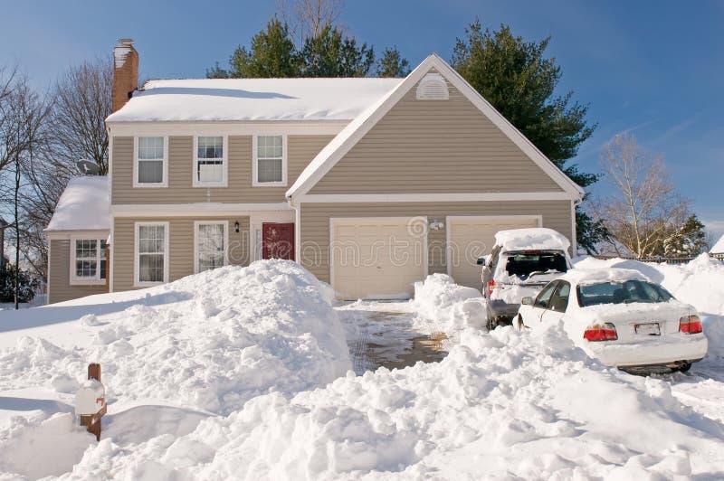 Casa y coches después de la tempestad de nieve imagen de archivo
