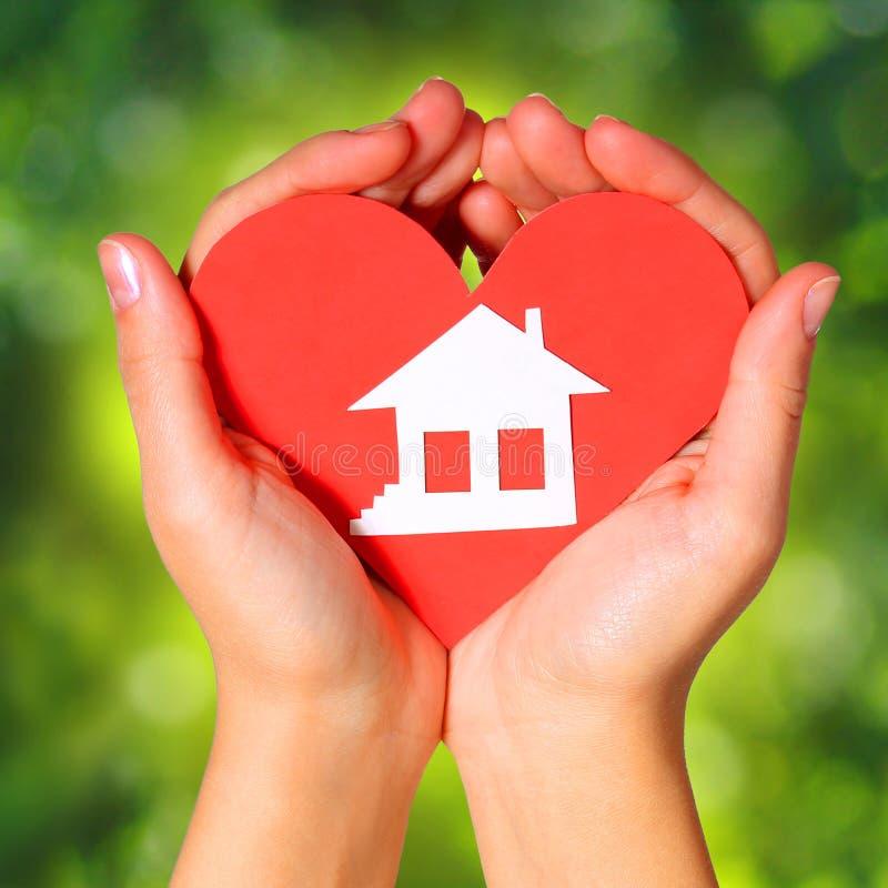 Casa y corazón de papel en manos femeninas imagen de archivo