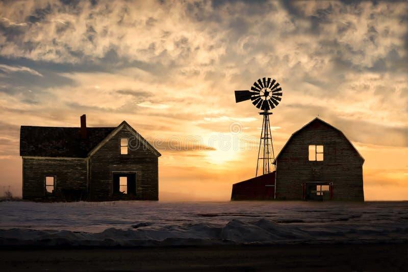 Casa y granero silhoetted abandonados viejos con puesta del sol hermosa fotos de archivo libres de regalías