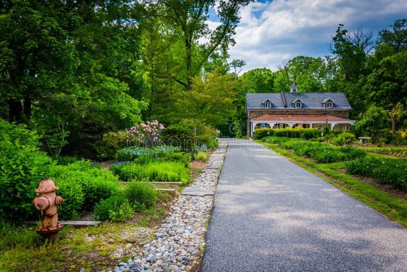 Casa y jardines a lo largo de una trayectoria en el arboreto de Cylburn, en Baltimor foto de archivo libre de regalías