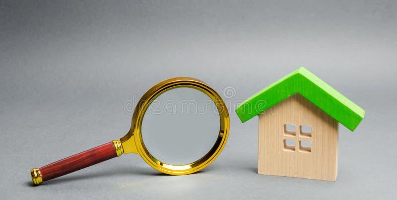 Casa y lupa de madera miniatura Valoraci?n casera Evaluaci?n de la propiedad Casa que busca concepto Opción de la ubicación para fotos de archivo libres de regalías