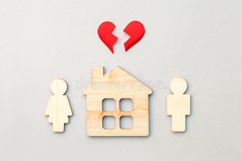 Casa y modelos de madera del hombre y de la mujer con el corazón quebrado rojo, el divorcio, el final de la relación y el concept imagen de archivo