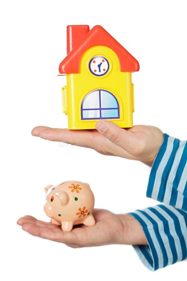 Casa y moneybox en manos foto de archivo