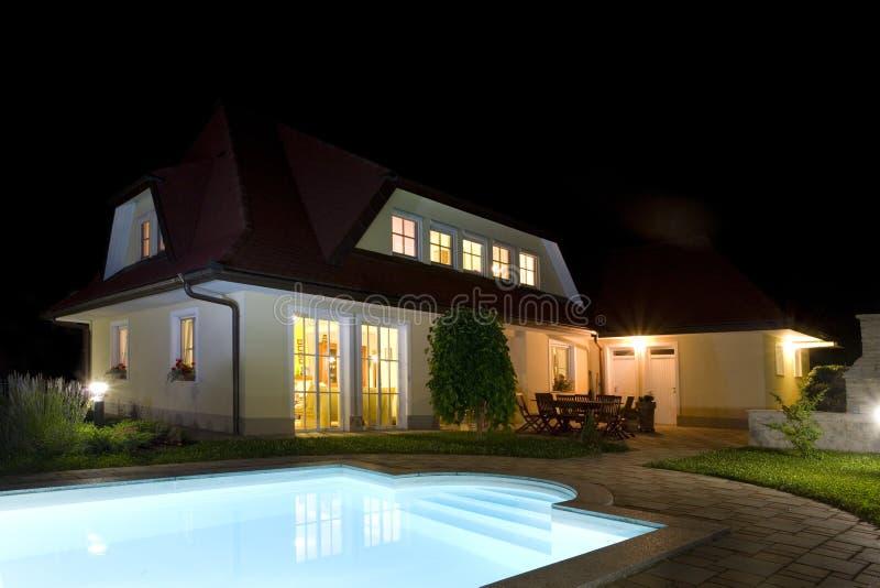 Casa y piscina en la noche fotografía de archivo libre de regalías