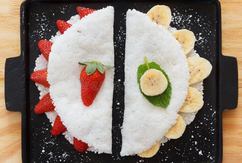 Casabe (bammy, beiju, bob) from cassava (tapioca). Casabe (bammy, beiju, bob, biju) - flatbread made from cassava (tapioca) with strawberry and banana on pun royalty free stock photo