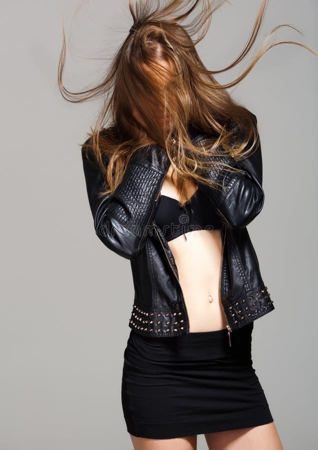 Casaco de cabedal vestindo modelo 'sexy' e saia preta que levantam a forma fotografia de stock