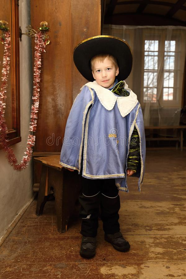 Casaco do menino novo e chapéu vestindo do mosqueteiro fotografia de stock royalty free