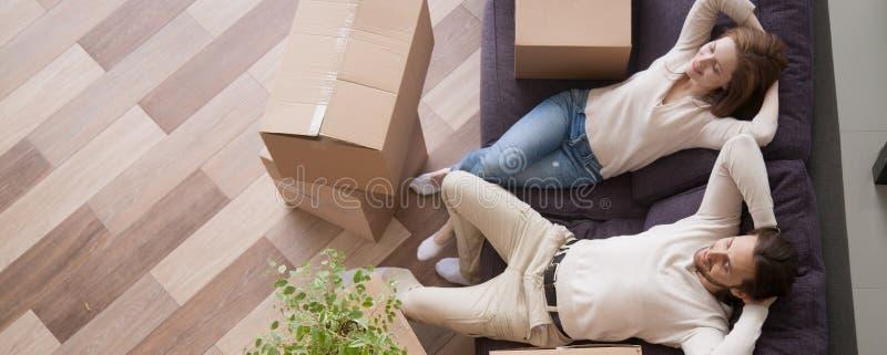 Casal acima da vista que descansa no sofá em dia movente foto de stock royalty free