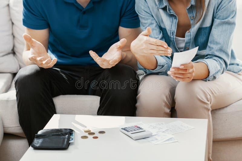 Casal anônimo sentado em sua sala calculando o dinheiro que eles têm para pagar contas imagem de stock royalty free