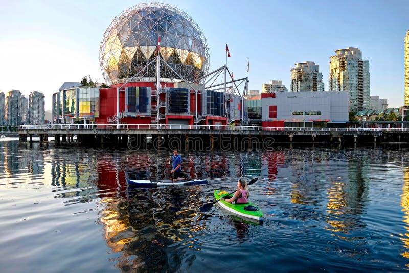 Casal ativo que rema e que kayaking na baía inglesa perto do mundo da ciência no verão foto de stock