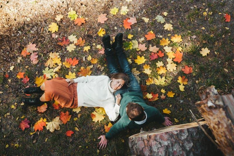 Casal autêntico aproveita o tempo juntos deitado no gramado com folhas vermelhas e amarelas de outono imagem de stock royalty free