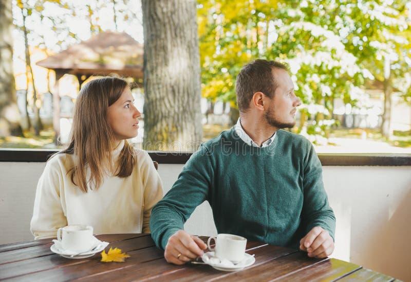 Casal bonito olhando de lado enquanto tomava café da manhã e bebe chá no jardim de outono fotografia de stock