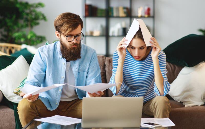 Casal com documentos e portátil dos recibos das contas em casa fotos de stock