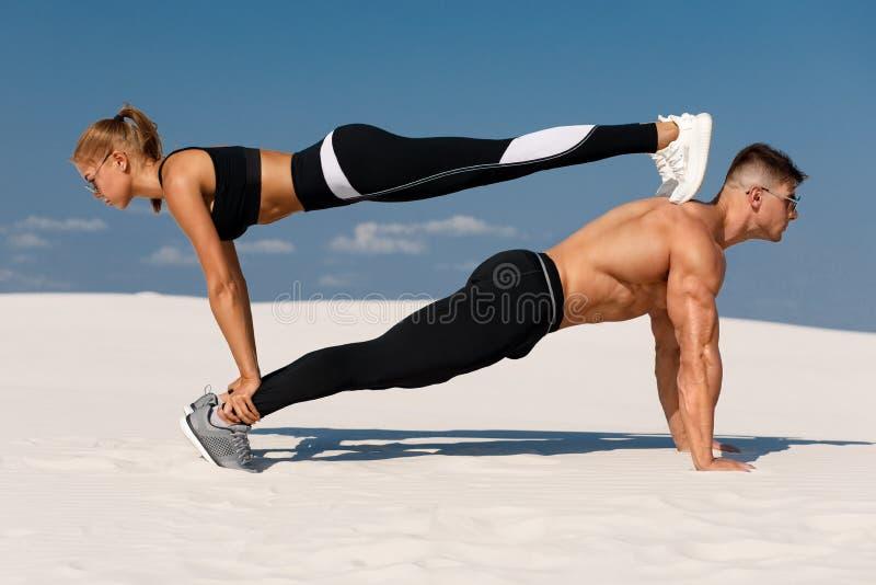 Casal desportivo fazendo exercício de aplainamento ao ar livre Belo atleta e trabalho feminino fotos de stock royalty free
