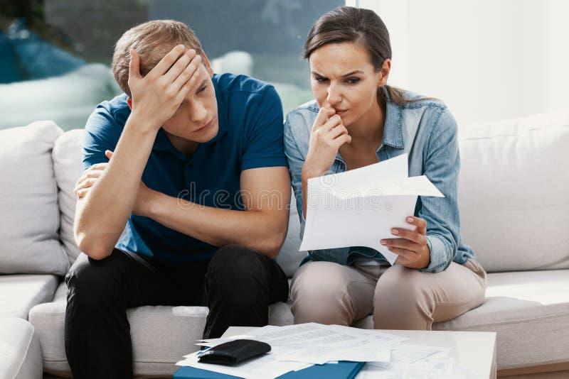 Casal em estresse que parece frustrado, não tendo dinheiro para pagar suas dívidas, gerenciando o orçamento familiar juntos fotografia de stock royalty free