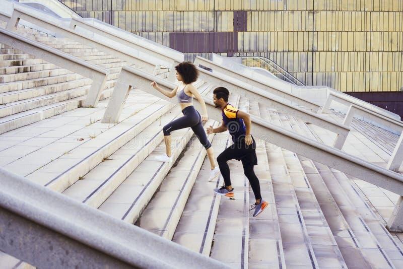 Casal esportivo interracial subindo escadas fotografia de stock royalty free