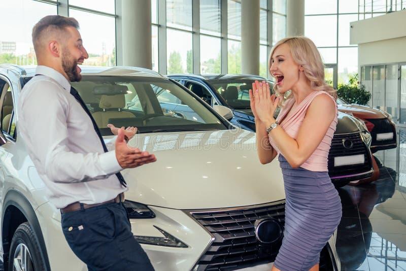 Casal feliz em frente ao carro novo, homem cobriu os olhos da esposa no banheiro automóvel-presente surpreendido fotografia de stock