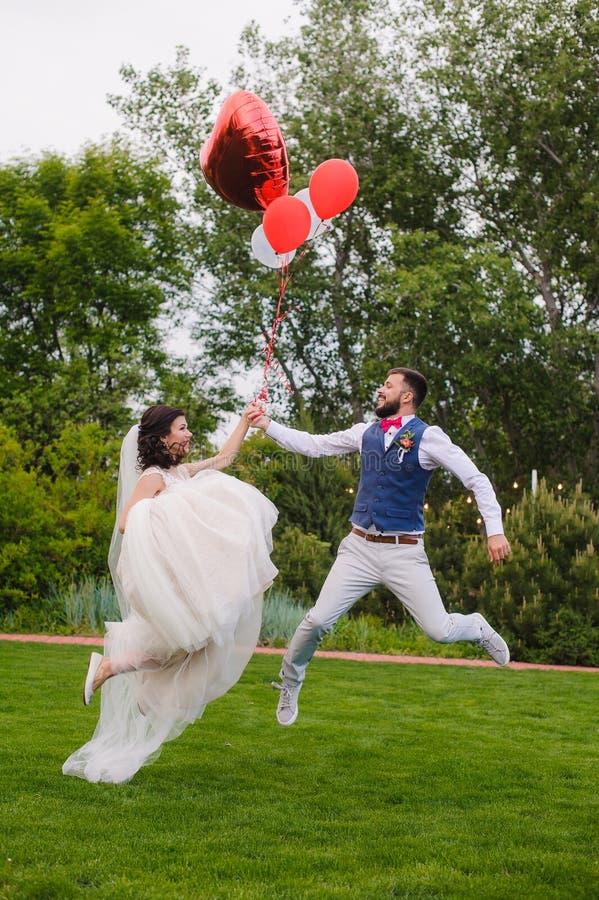 Casal feliz que salta com balões vermelhos fotografia de stock royalty free