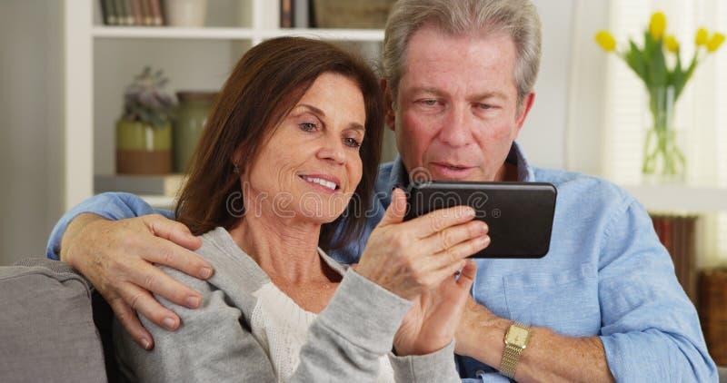 Casal feliz que usa o smartphone fotografia de stock