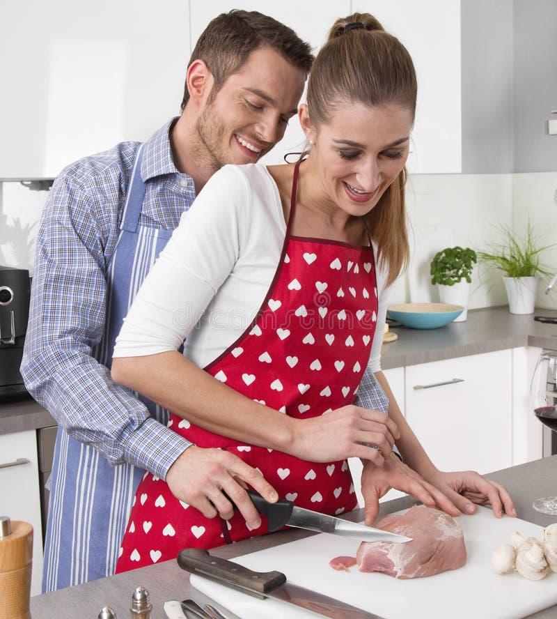 Casal fresco novo na cozinha que cozinha junto o assado imagem de stock