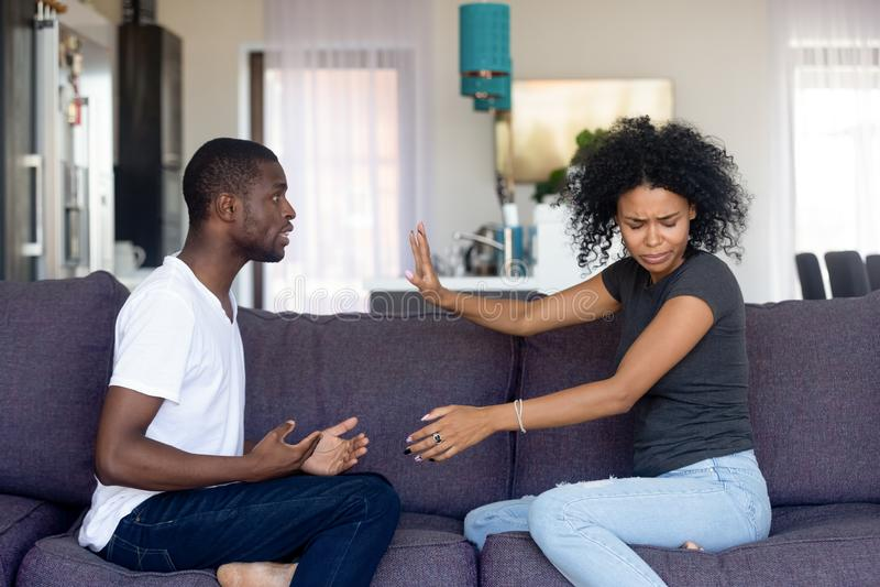 Casal infeliz africano que senta-se no sofá que discute em casa fotos de stock royalty free