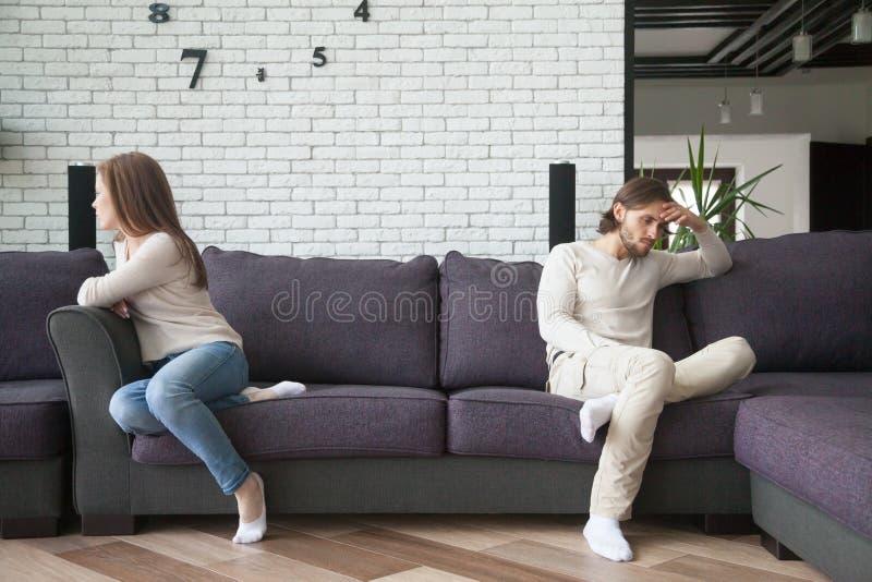 Casal infeliz na discussão que senta-se no sofá fotografia de stock royalty free