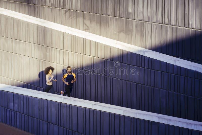 Casal interracial corre na cidade fotografia de stock