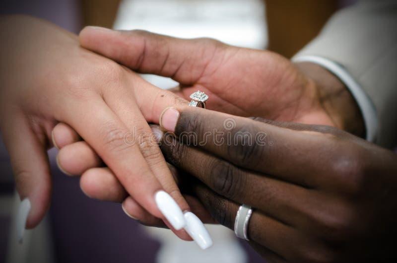 Casal interracial trocando alianças na cerimônia de casamento fotos de stock
