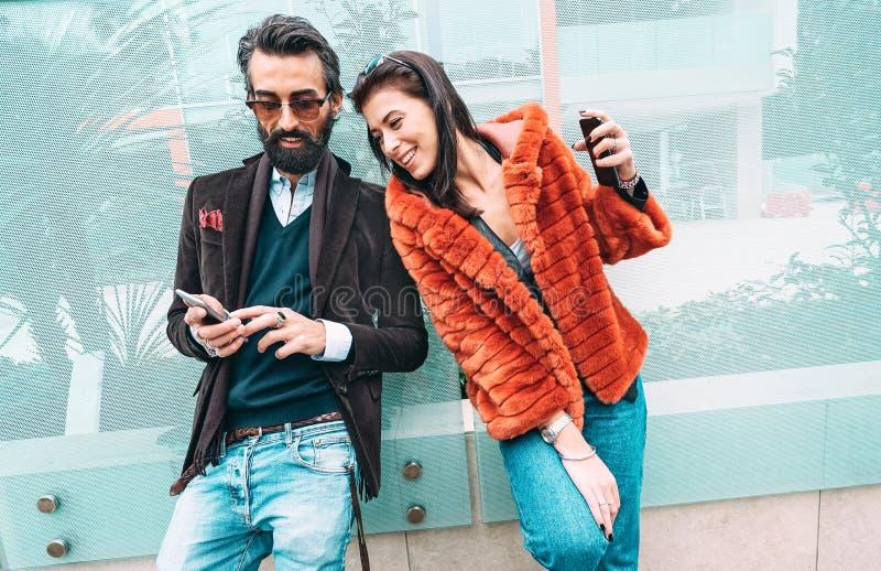 Casal moderno hipster se divertindo usando o celular inteligente fora - Conceito de interação social com amigos compartilhando fo imagem de stock