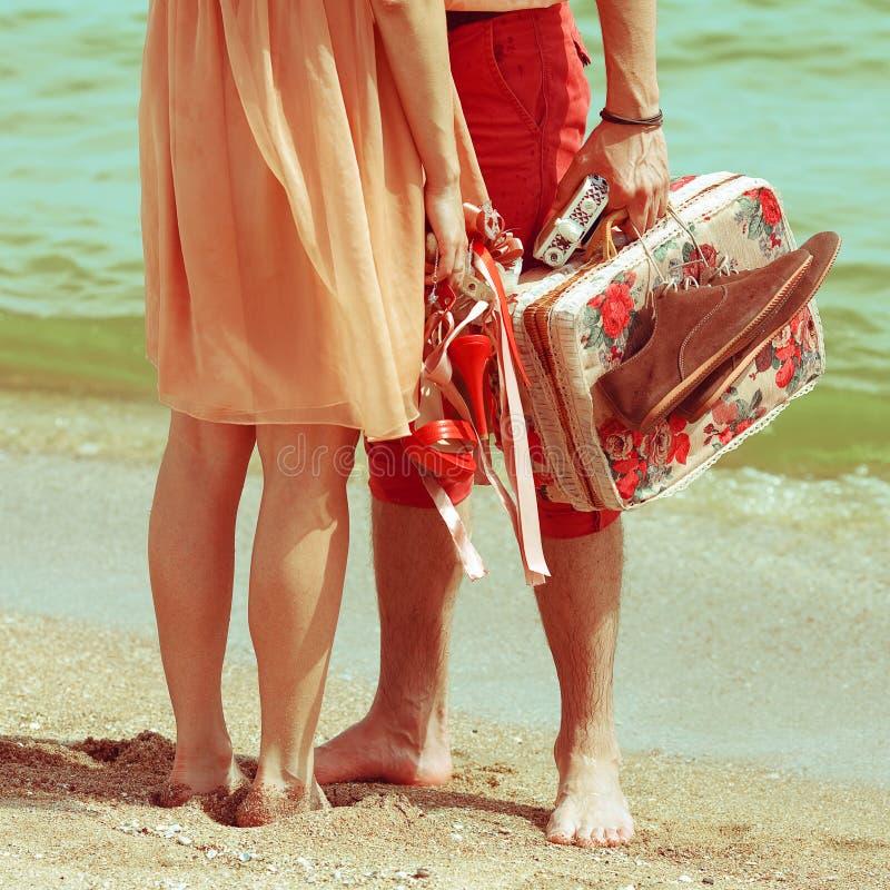 Casal novo que está junto na praia que guarda-se imagem de stock