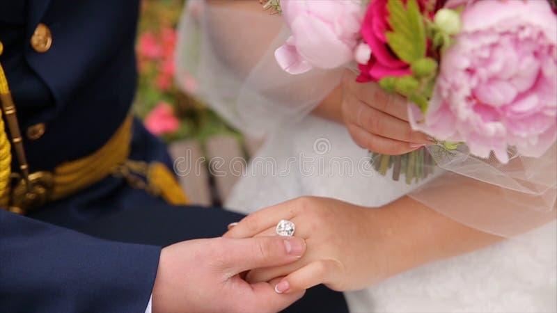 Casal novo que guarda as mãos, dia do casamento da cerimônia Feche acima do noivo Put a aliança de casamento na noiva fotos de stock royalty free