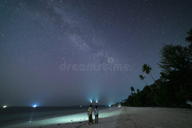 Casal olhando estrelas e o caminho leitoso na praia de areia, luz de tocha no céu noturno, vista traseira, pessoas reais Indonési imagens de stock