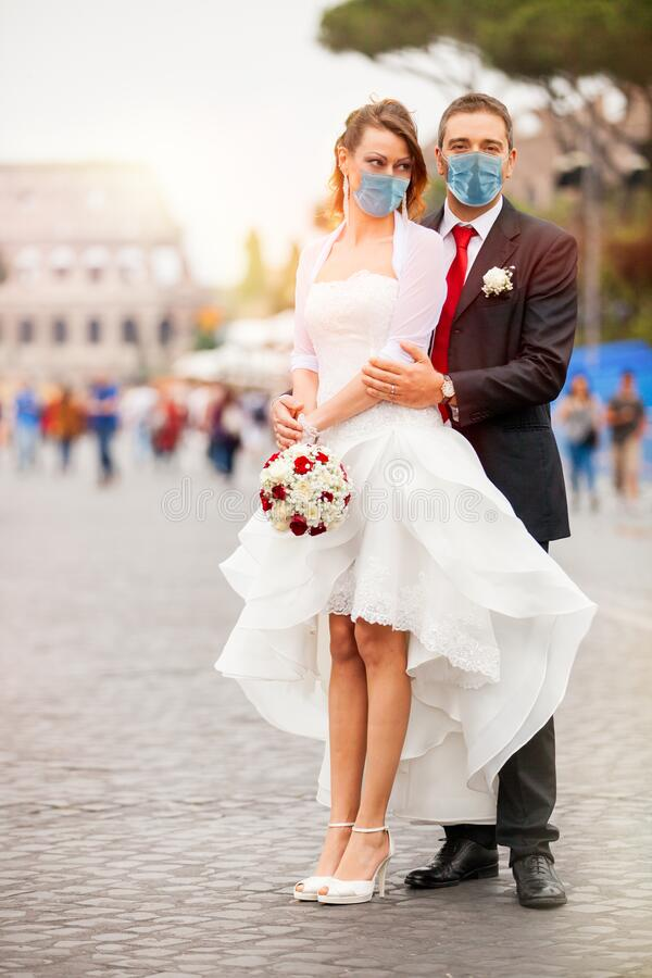 Casal recém casado com máscara no dia do casamento Na rua com o Coliseu ao fundo em Roma, Itália A imagens de stock