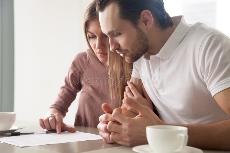 Casal sério com os papéis, considerando a oferta de empréstimo, calc fotografia de stock