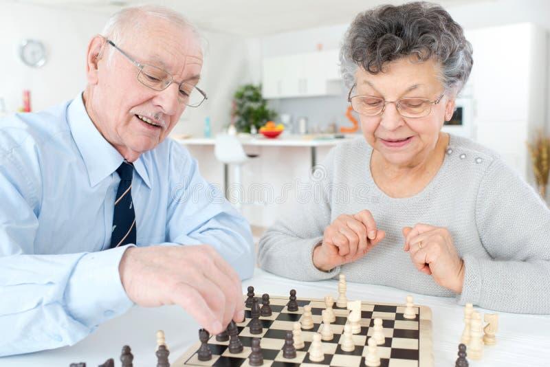 Casal superior que joga a xadrez em casa imagens de stock
