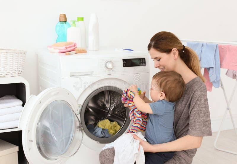 Casalinga con il piccolo figlio che fa lavanderia fotografia stock libera da diritti