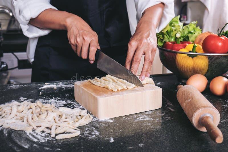 Casalinga femminile che produce pasta casalinga con farina e le uova più fotografia stock