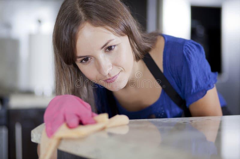 Casalinga graziosa che pulisce la cucina fotografie stock