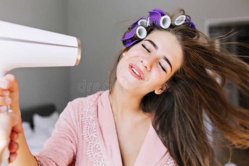 Casalinga graziosa del ritratto in accappatoio rosa con il bigodino a casa Esamina goduta dei capelli di essiccazione fotografia stock libera da diritti